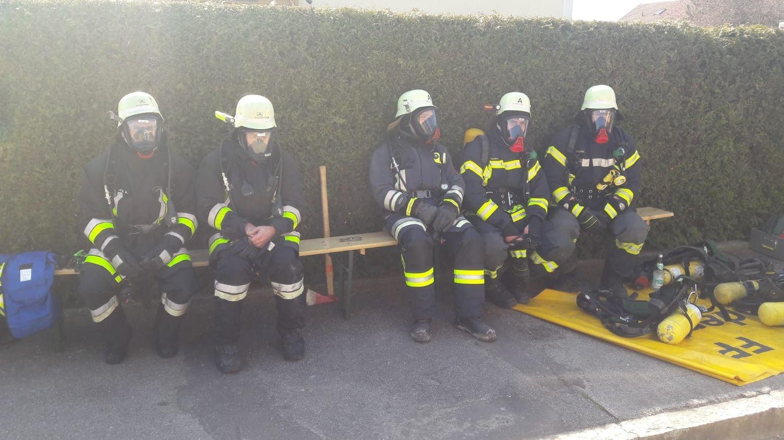 Feuerwehrmänner sitzen nach dem Großeinsatz in Bodenkirchen auf einer Bank
