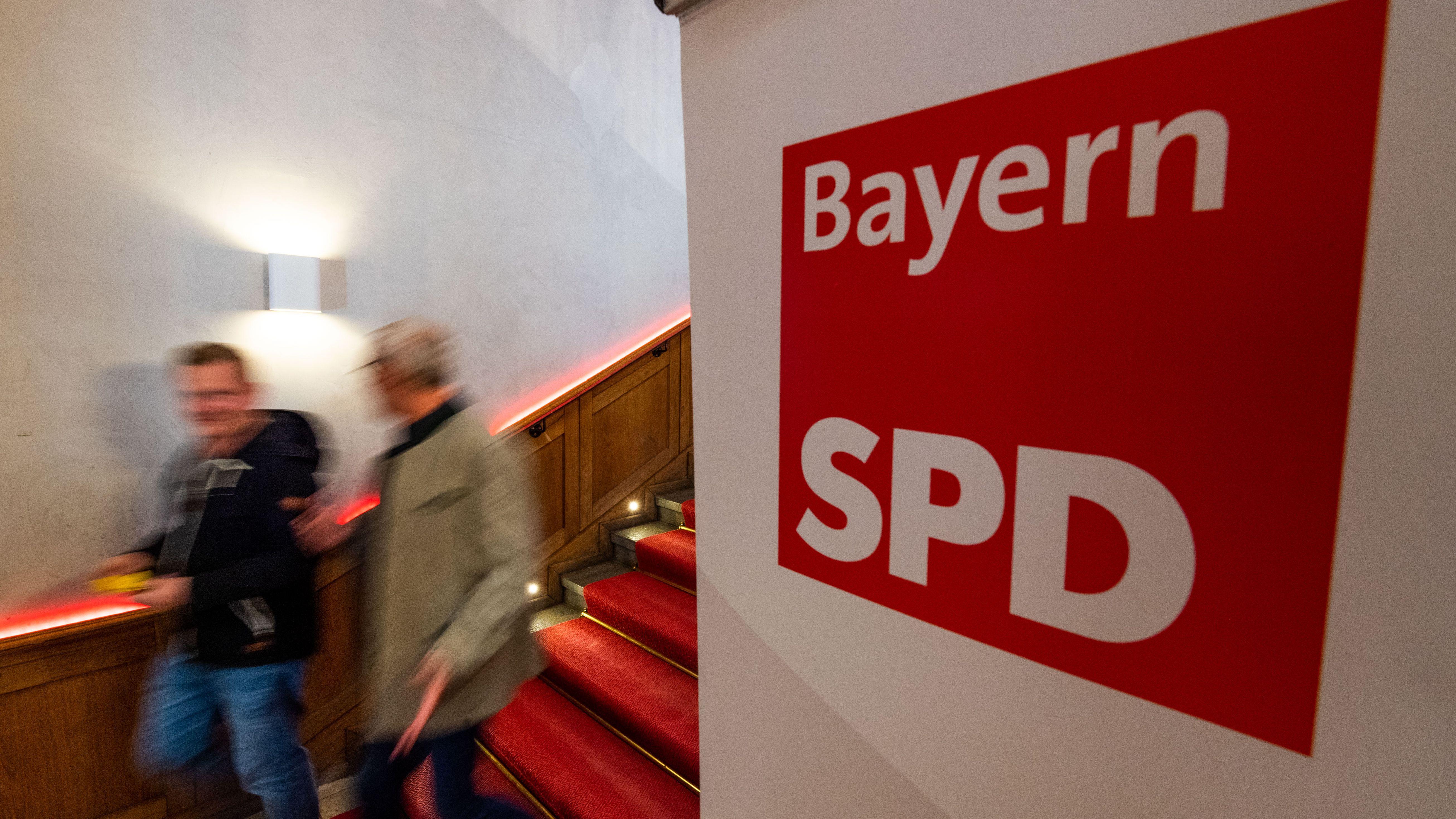 Zwei Männer gehen am Logo der SPD Bayern vorbei.
