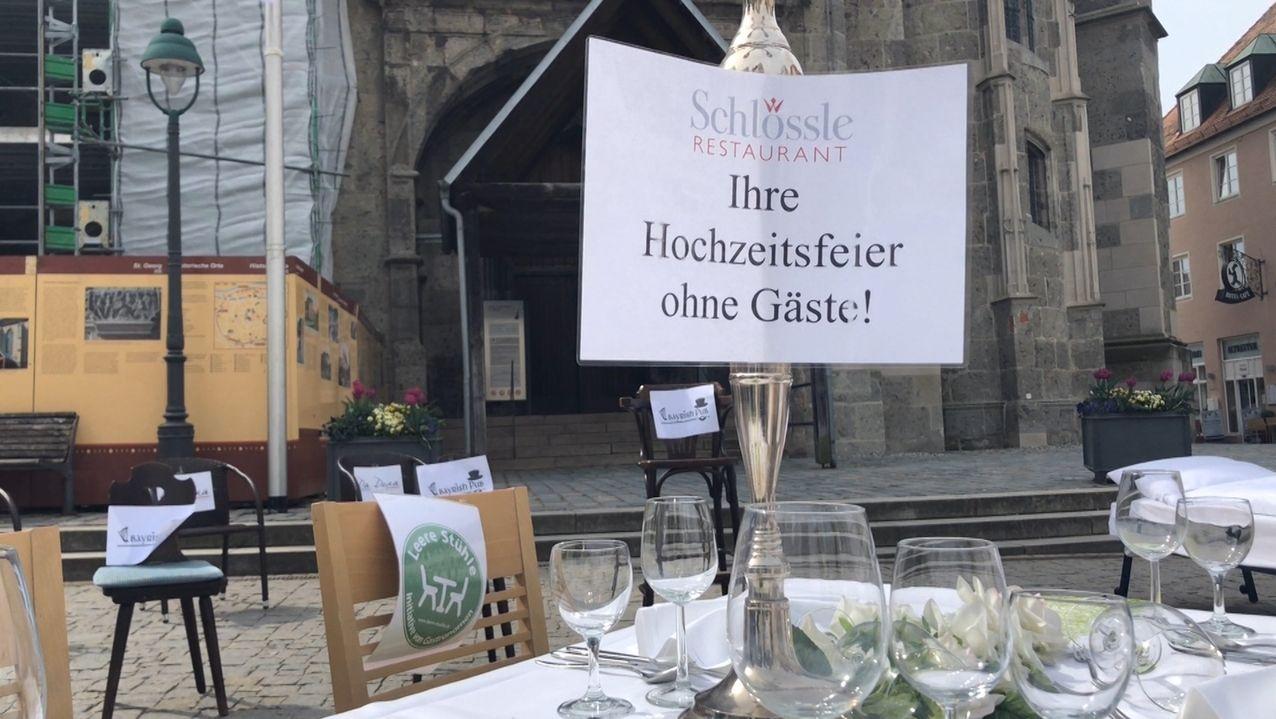 """Auf dem Nördlinger Markplatz: Auf einem festlich gedeckten Tisch  steht ein Schild auf dem steht: """"Ihre Hochzeitsfeier ohne Gäste"""". Gastronomen protestieren damit gegen die strengen Corona-Regeln."""