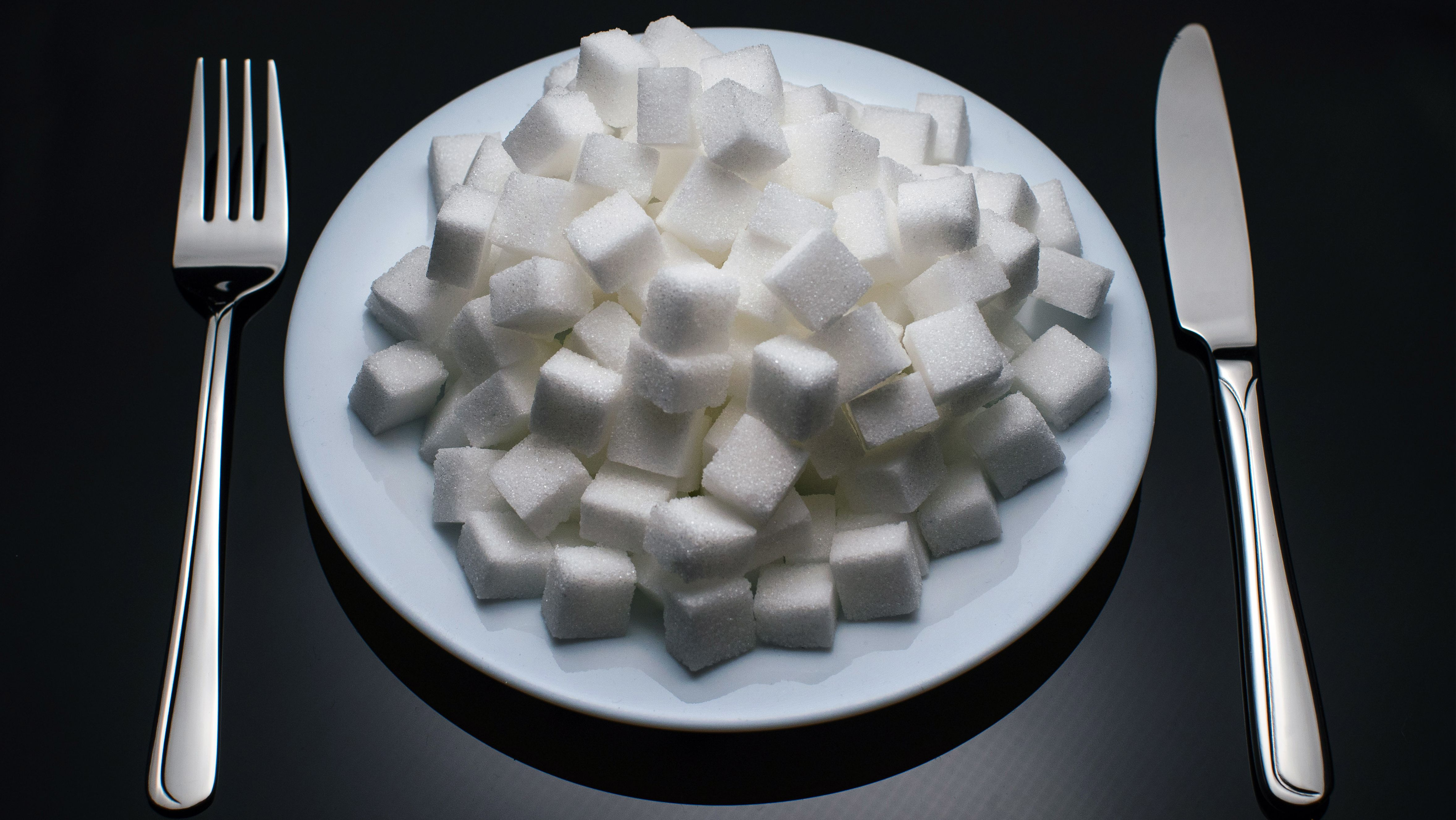 Teller mit Zuckerwürfeln und Besteck (Symbolbild: Fettleibigkeit)