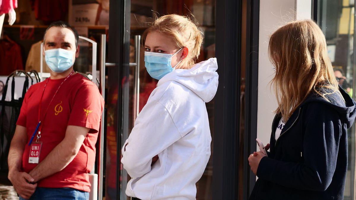 Zwei Jugendliche mit Maske warten vor einem Geschäft