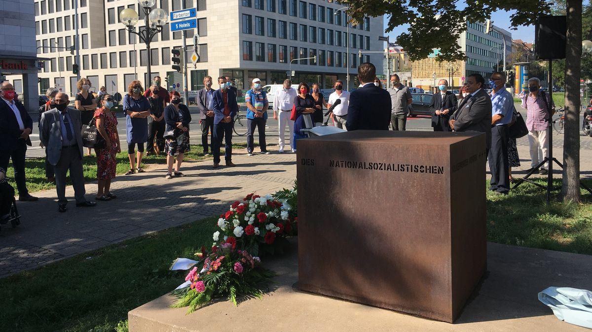 Menschen stehen im Gedenken vor dem Mahnmal für die von den Nationalsozialisten ermordeten Sinti und Roma in Nürnberg.