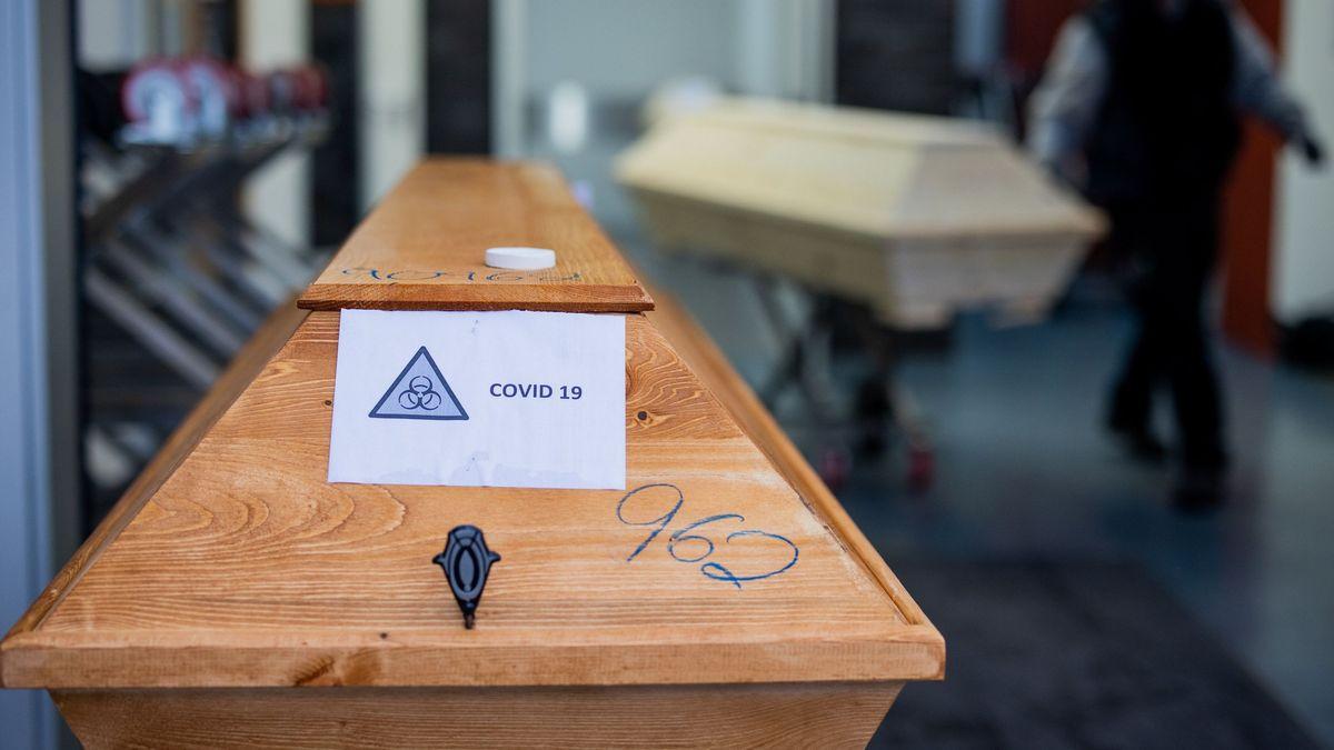 """Symbolbild: Ein Sarg mit der Aufschrift """"Covid 19"""" wird von einem Bestatter in ein Krematorium eingeliefert."""