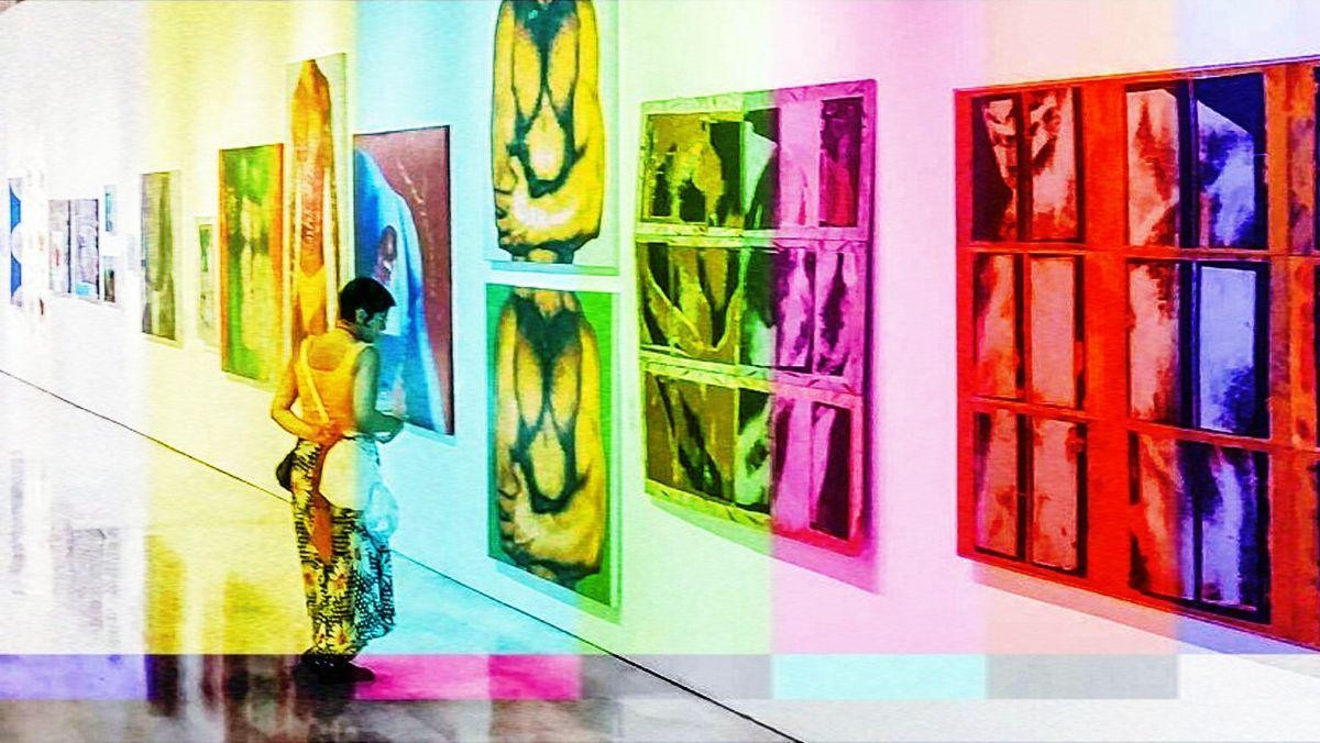 Eine Frau in gelbem Trägertop und Rock sieht sich in einer Galerie starkfarbige Bilder an