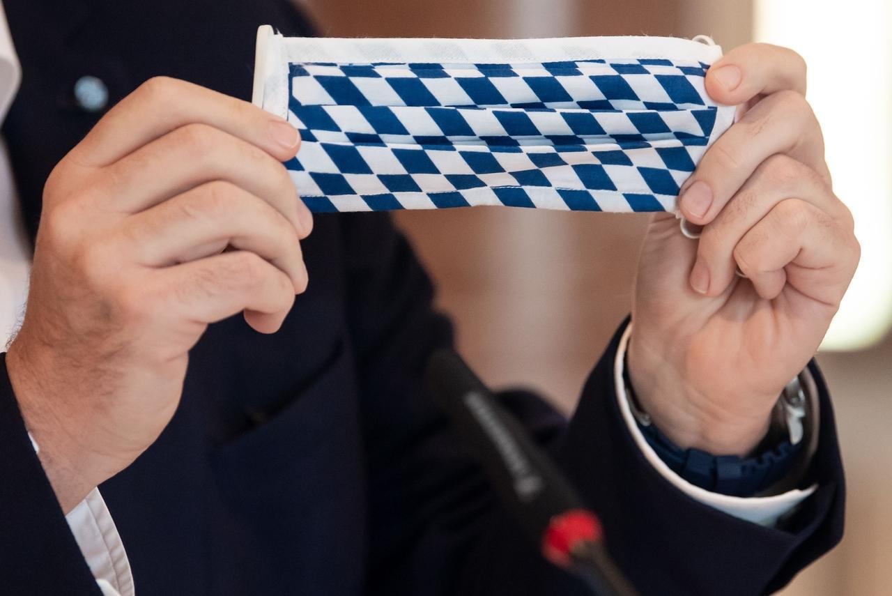 Ministerpräsident Markus Söder hält eine Community Maske aus Stoff mit den bayerischen Rauten in den Händen