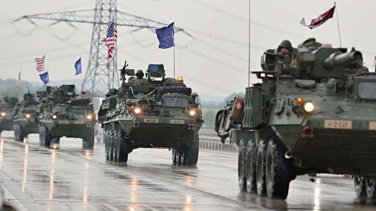 Viele Militärfahrzeuge mit Nato- und US-Flaggen fahren hintereinander auf einer Straße.