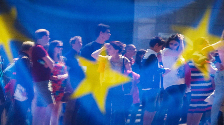Menschen spiegeln sich in einem Fenster mit einer europäischen Flagge im Europäischen Parlament.