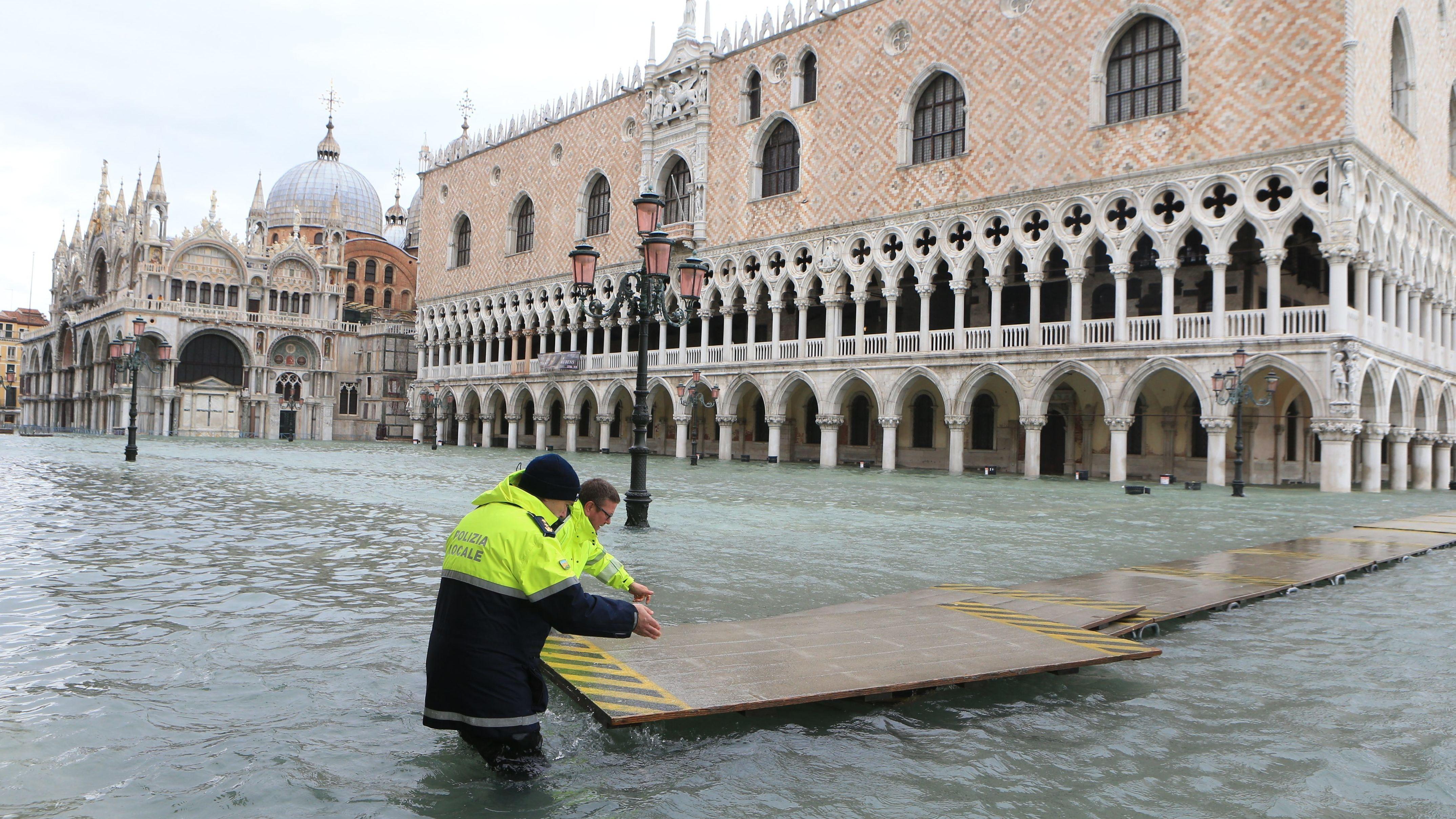 Helfer der Polizei in Venedig verlegen einen schwimmenden Übergang für Fußgänger