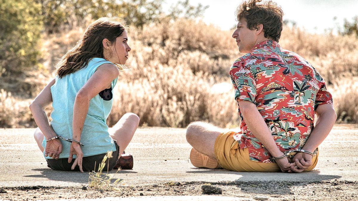 Eine Frau und ein Mann sitzen auf einer Straße. Beide haben hinter dem eigenen Rücken die Hände mit Handschellen gefesselt.