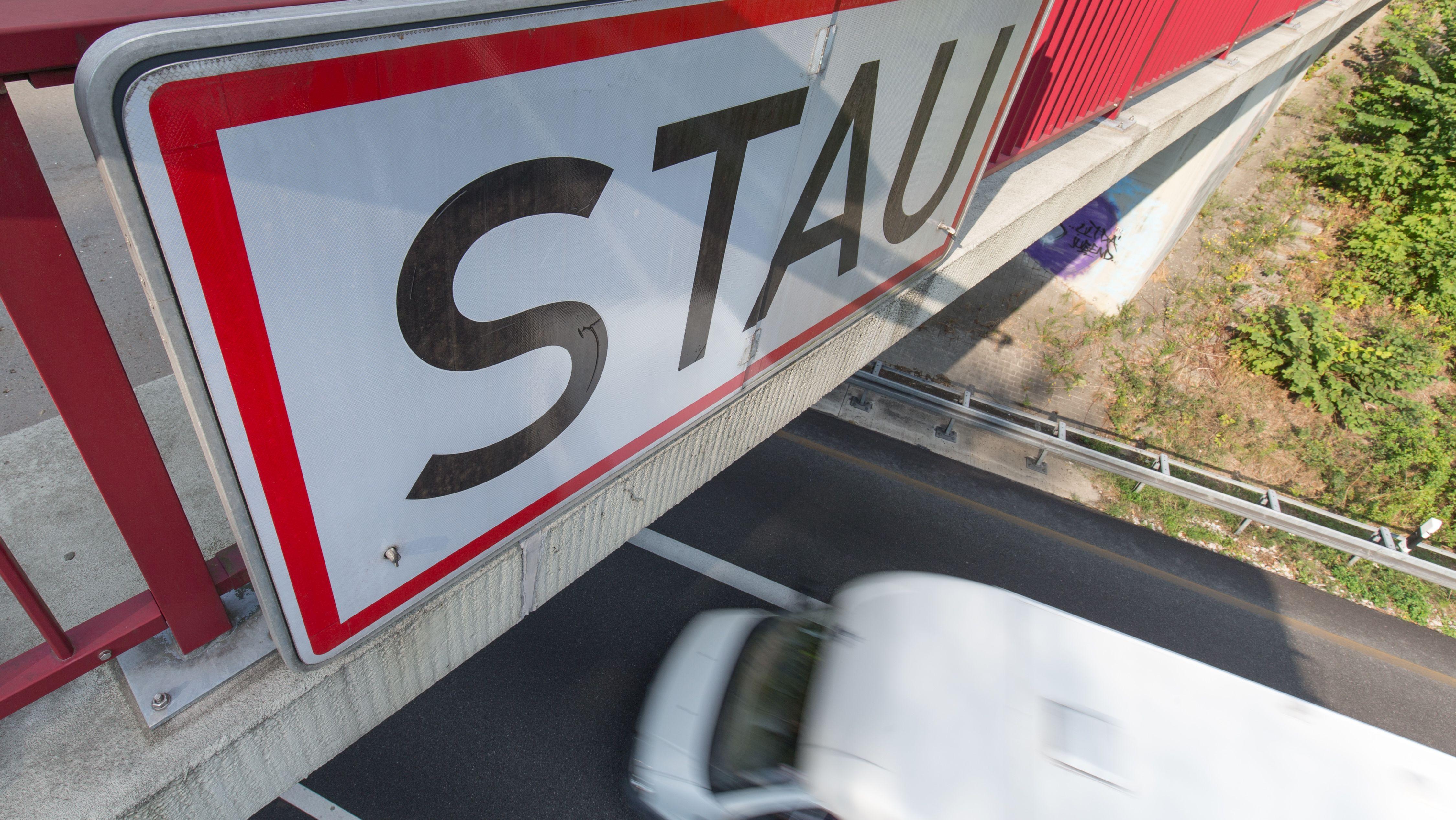 """Ein Schild """"Stau"""" ist auf einer Autobahnbrücke angebracht"""