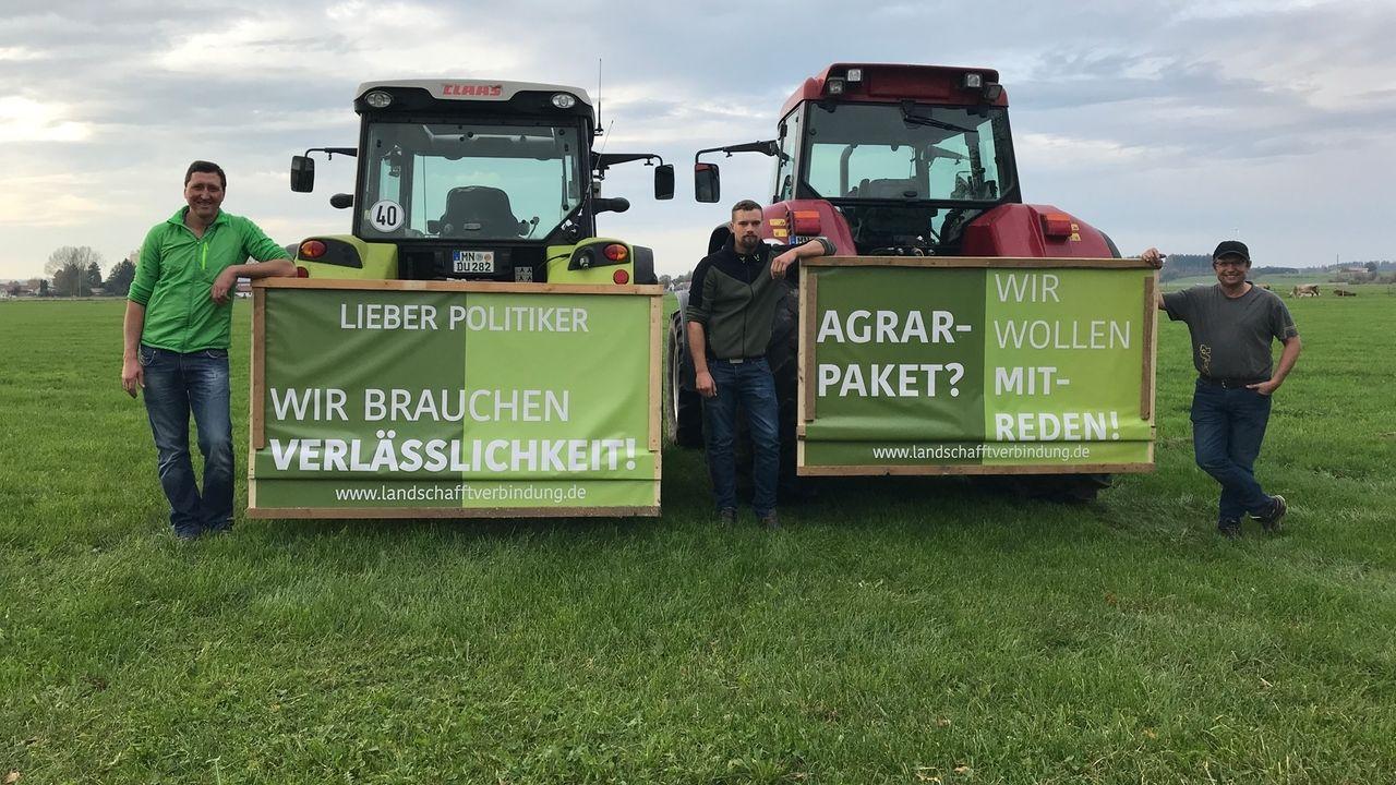 """Allgäuer Landwirte posieren vor Traktoren, an denen Banner befestigt sind. Darauf ist zu lesen: """"Lieber Politiker, wir brauchen Verlässlichkeit!"""" und """"Agrarpaket? Wir wollen mitreden!"""""""