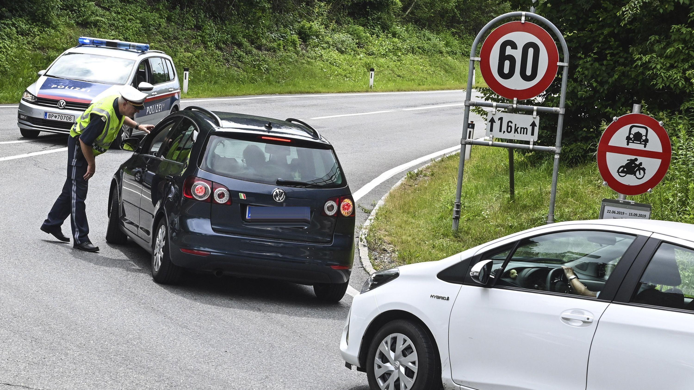 Ein österreichischer Polizist hält Autos auf einer Straße an