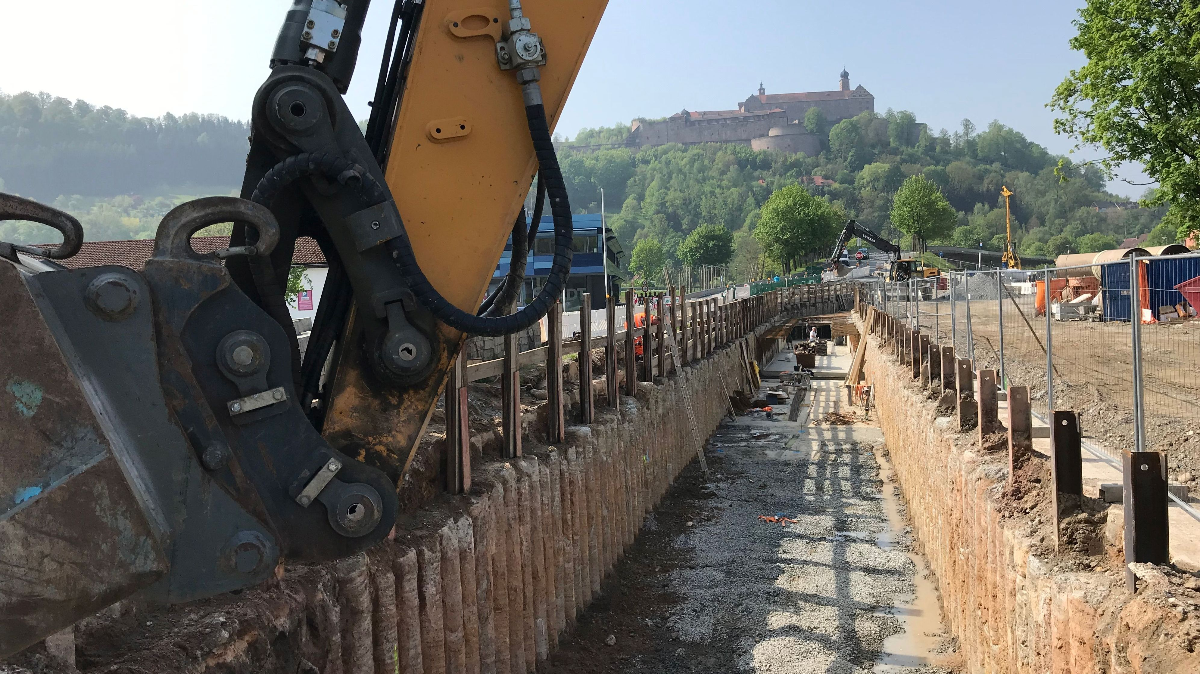 Ein Bagger hebt einen Kanal aus, im Hintergrund die Plassenburg von Kulmbach.
