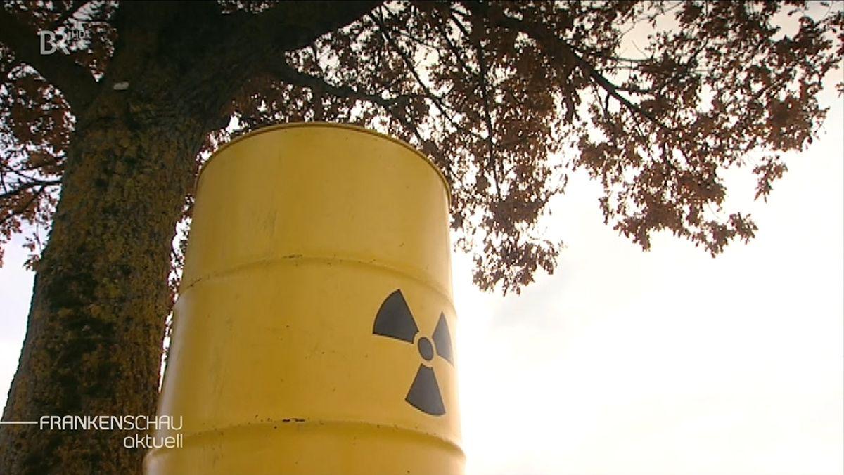 Eine gelbe mit dem schwarzen Symbol für Atomkraft steht vor einem Baum.