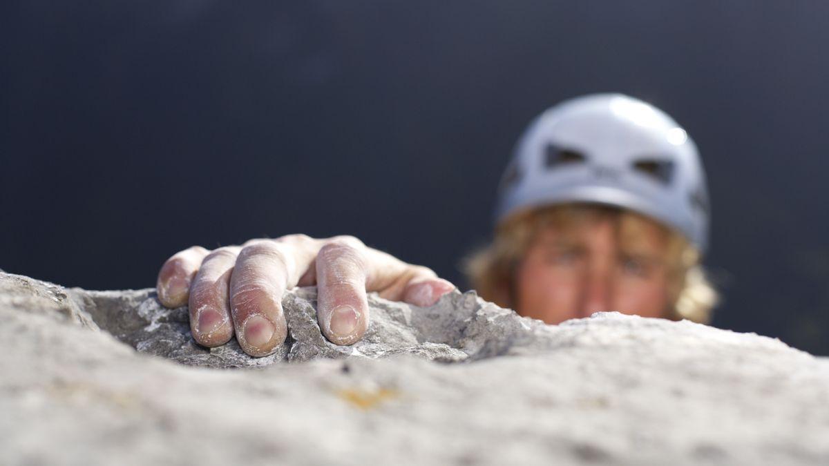 Ein Mann zieht sich beim Klettern eine Felswand hinauf. (Symbolbild)