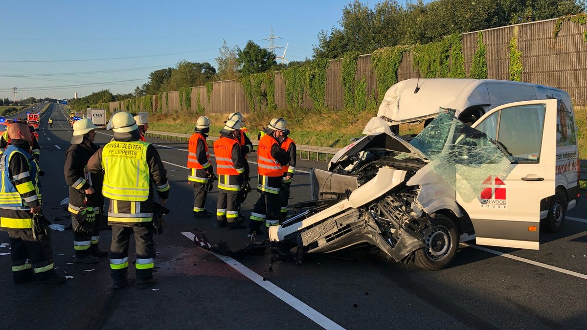 Helfer der Feuerwehr stehen auf der Autobahn vor einem schwer beschädigten Kastenwagen.