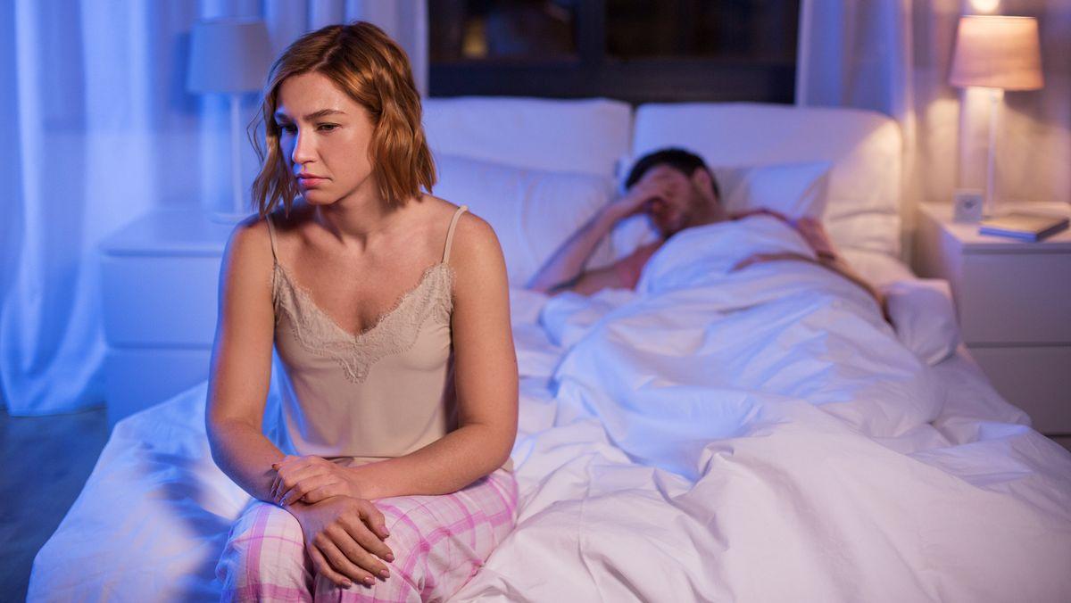 Eine junge Frau sitzt schlaflos auf der Bettkante