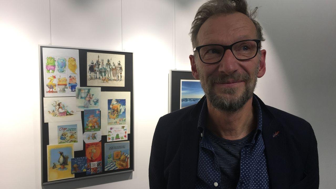 Der Illustrator von Kinderbüchern, Michael Schober, im schwarzen Jacket und schwarzer Brille steht neben einigen seiner bunten Illustrationen, die an der Wand der Stadtbücherei Bayreuth hängen.