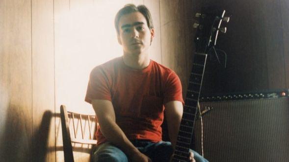 Ein Mann in rotem T-Shirt und Gitarre sitzt auf einem Stuhl.
