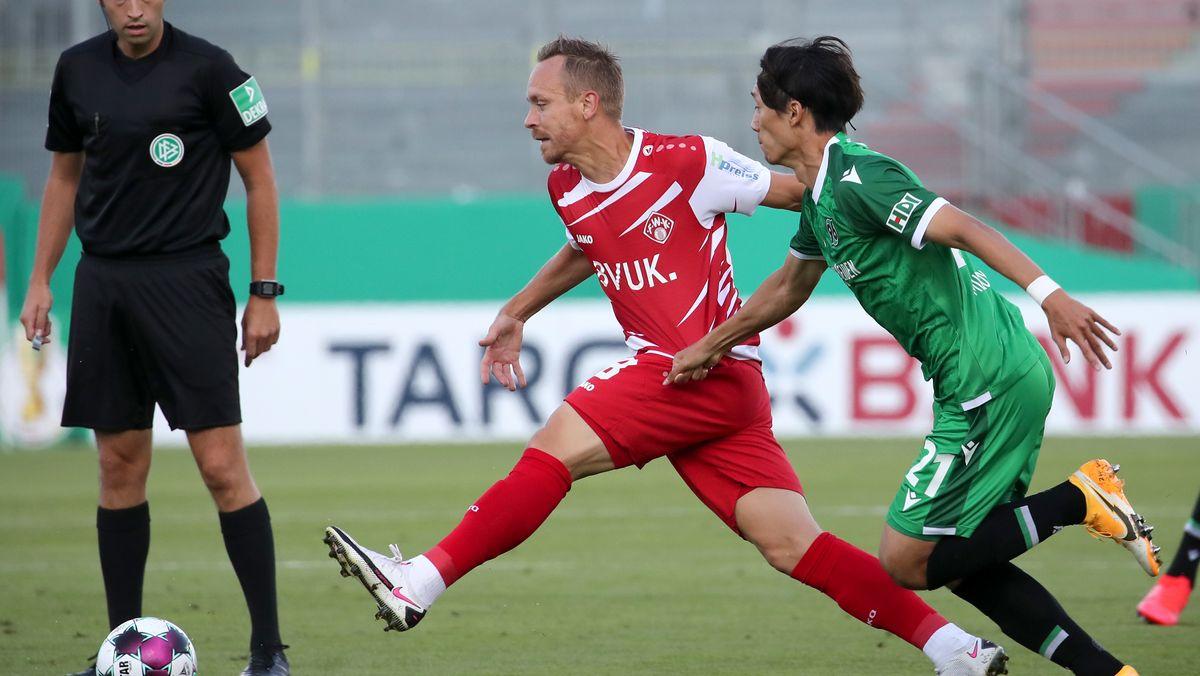 DFB-Pokal, Würzburger Kickers - Hannover 96, Arne Feick kämpft mit Sei Muroya von Hannover 96 um den Ball.
