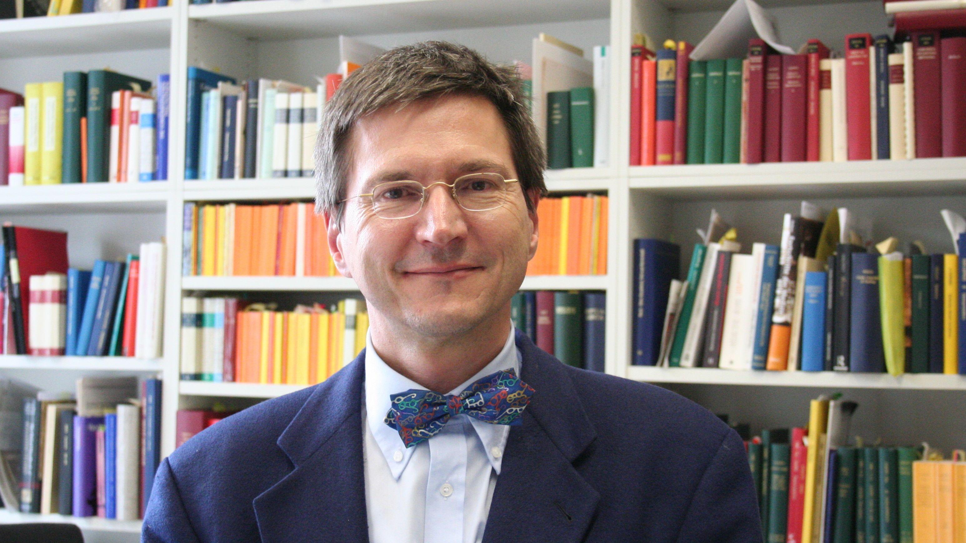 Porträt eines Mannes mit Brille, blauem Anzug und Fliege vor einem Bücherregal.