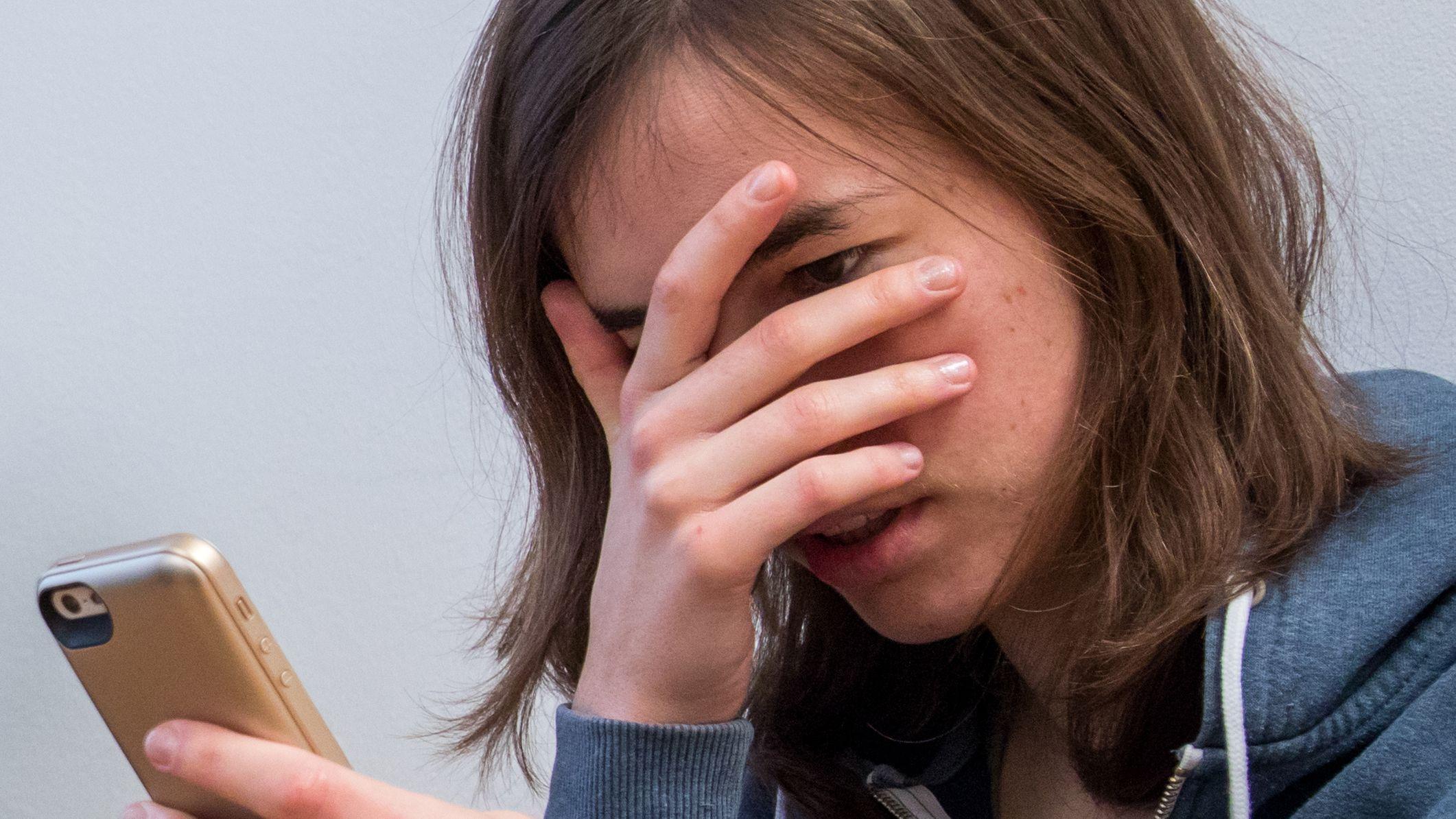 Mädchen schaut geschockt auf ihr Smartphone