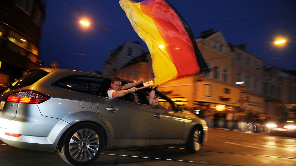 Fußball-Fans fahren mit einem Auto durch eine Innenstadt. Ein Mann schwenkt eine Fahne.