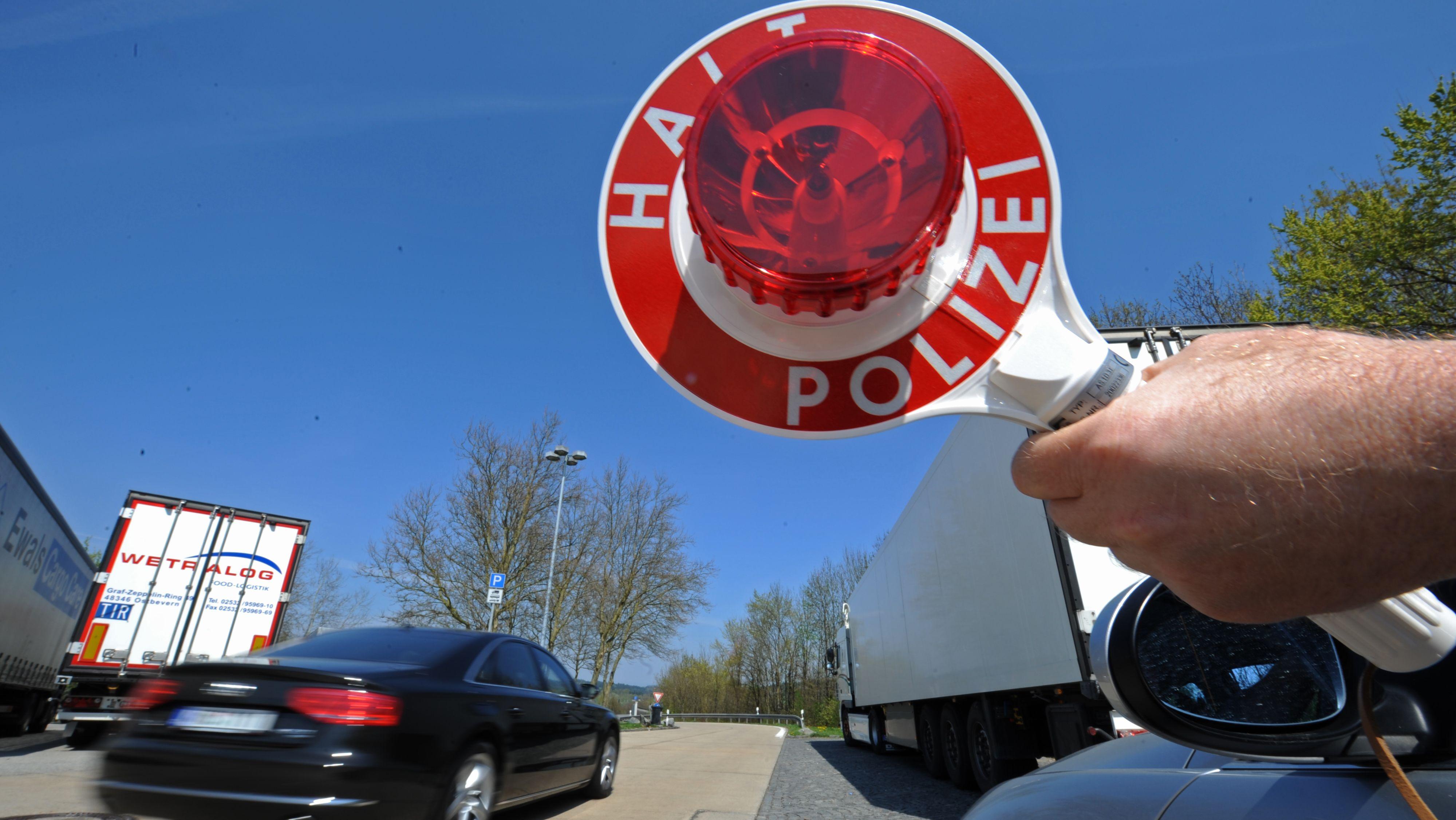 """Ein sogenannter Schleierfahnder hält auf der A3 nahe Passau eine Kelle mit dem Aufdruck """"Halt Polizei"""" aus einem Zivilfahrzeug der Polizei."""