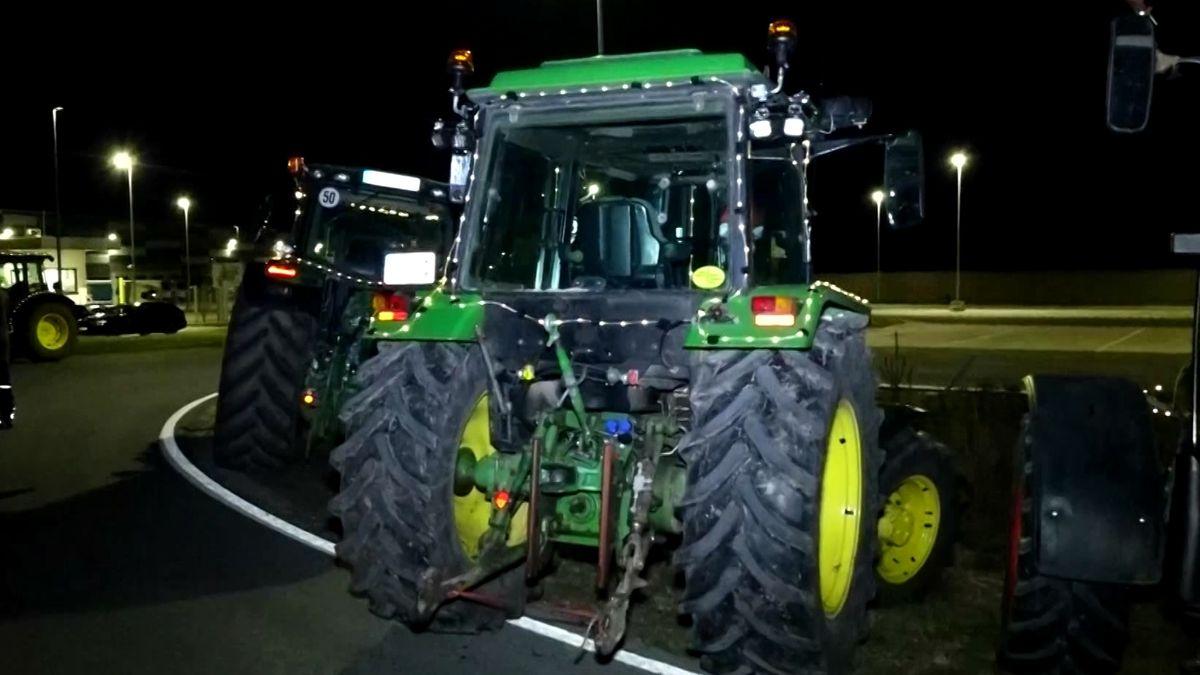 Traktoren versperren die Zufahrt zu einem Gelände, daneben parken Polizeifahrzeuge.