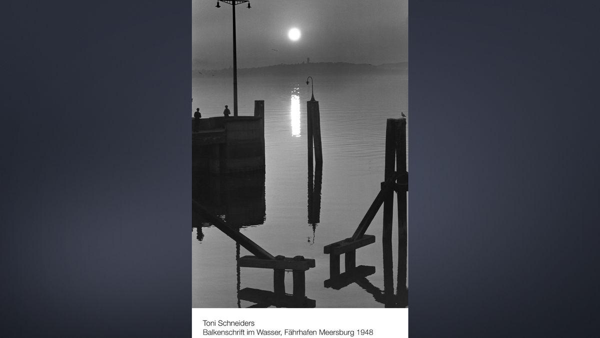 Schwazrweißaufnahme des Fährhafen Meersburg am Bodensee bei Sonnenuntergang