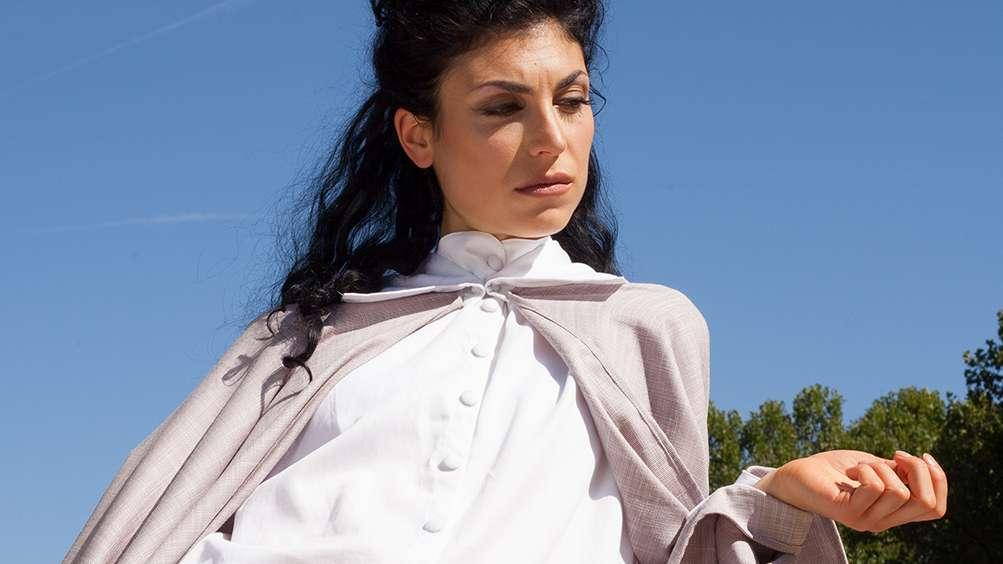 Frau mit weißer Bluse und beigem Mantel