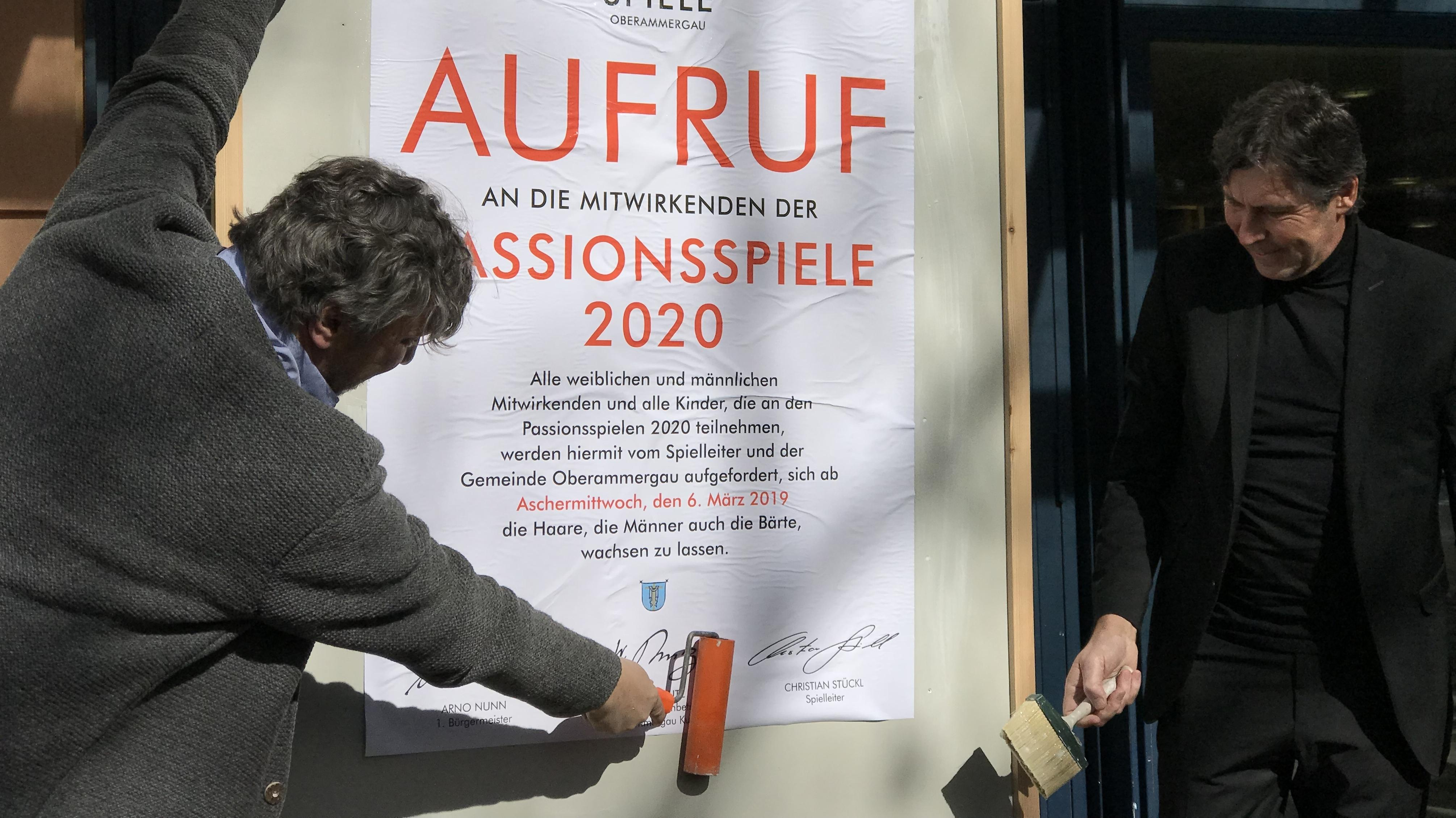 Passionsspielleiter Christian Stückl (l.) und Bürgermeister Bürgermeister Arno Nunn plakatieren den Haar- und Barterlass.