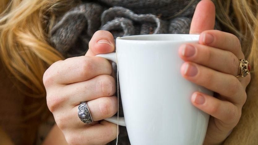 Frau hält Tasse Tee in der Hand