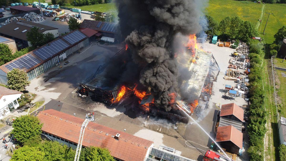 Feuerwehr löscht Großbrand, aus den Flammen steigt eine dichte schwarze Rauchwolke empor.