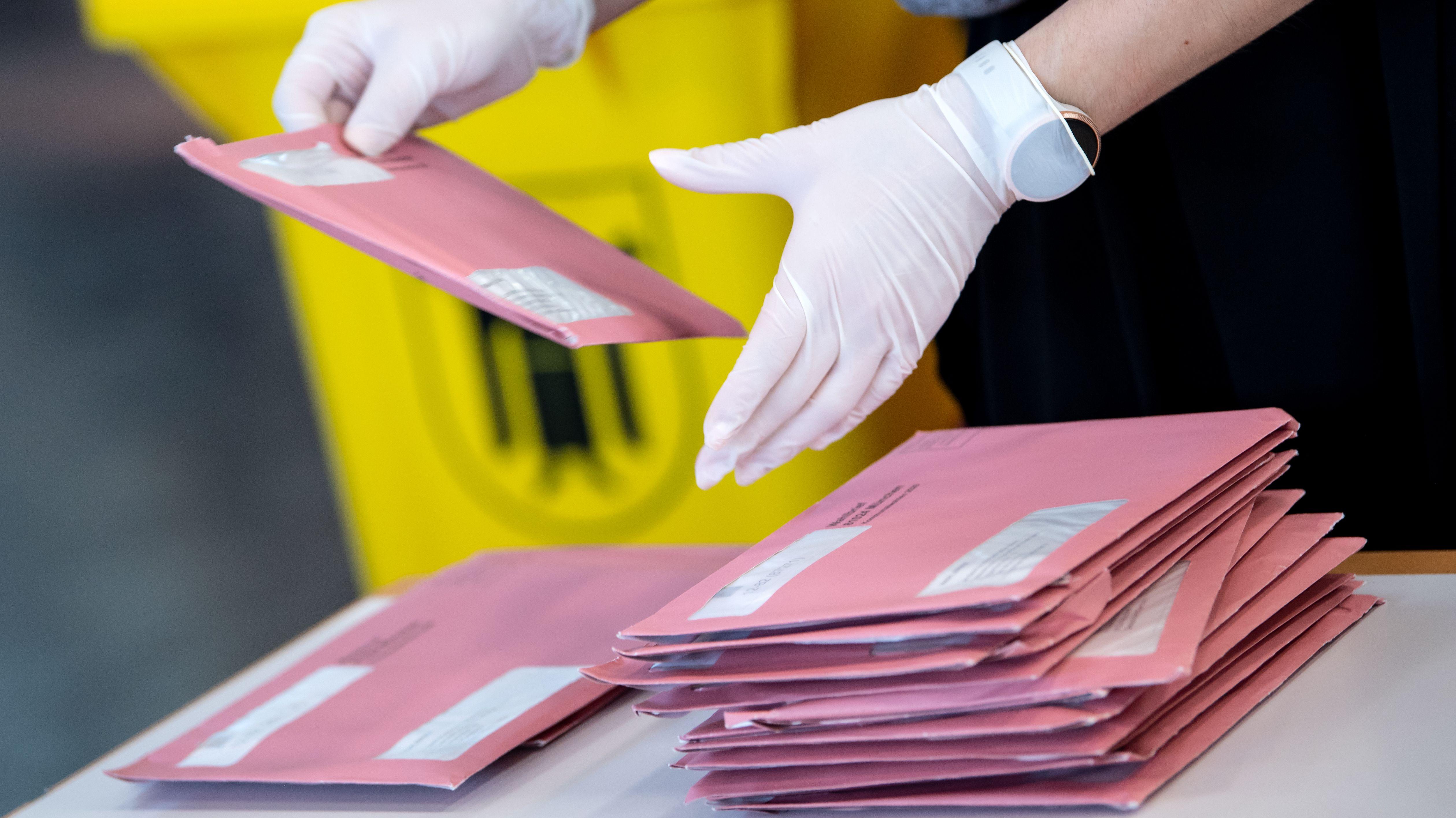 Ein Wahlhelfer zählt die Briefwahl aus.