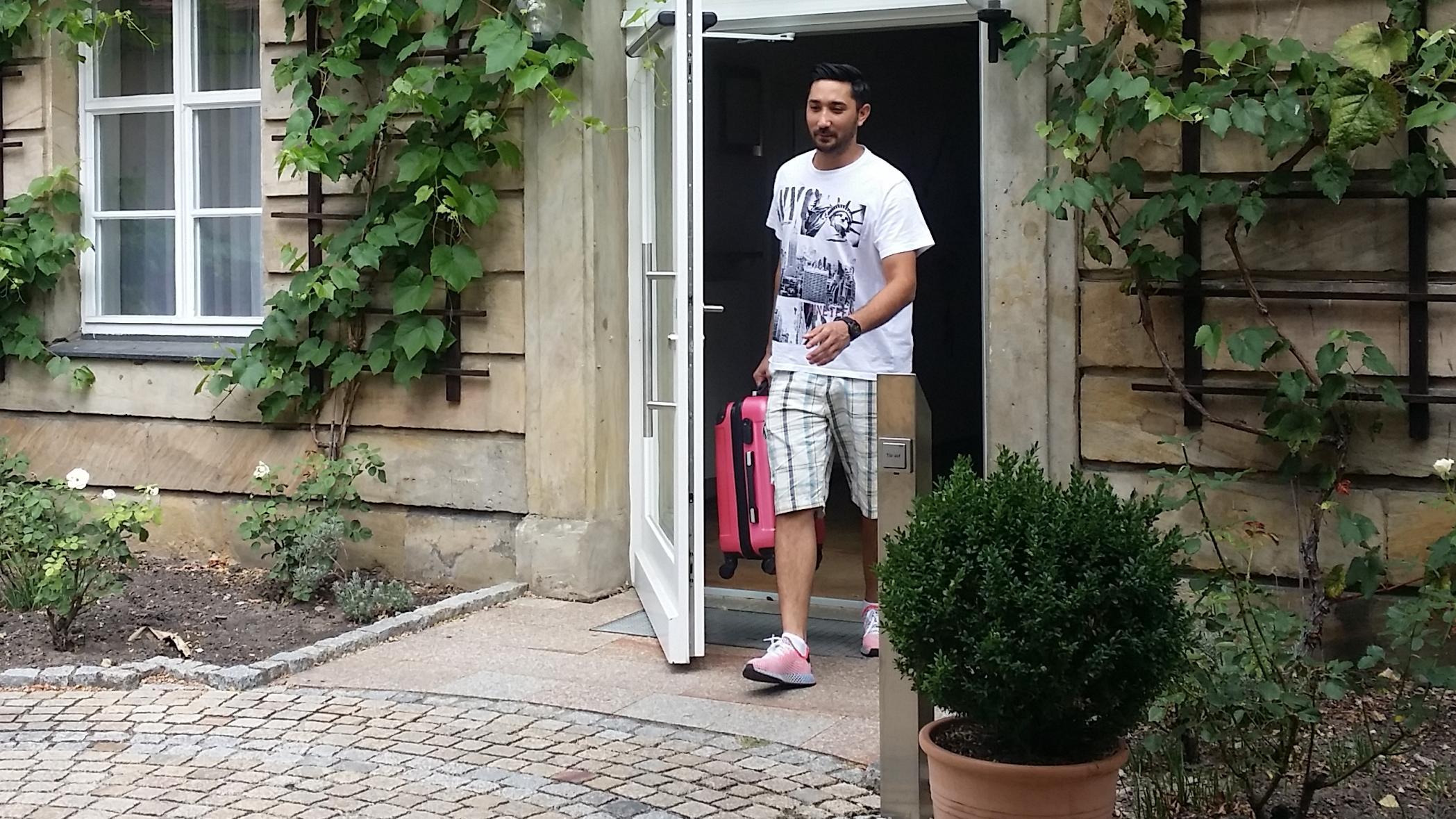 Ein junger Mann in kurzer Hose verlässt mit einem rosa Handkoffer ein Gebäude.