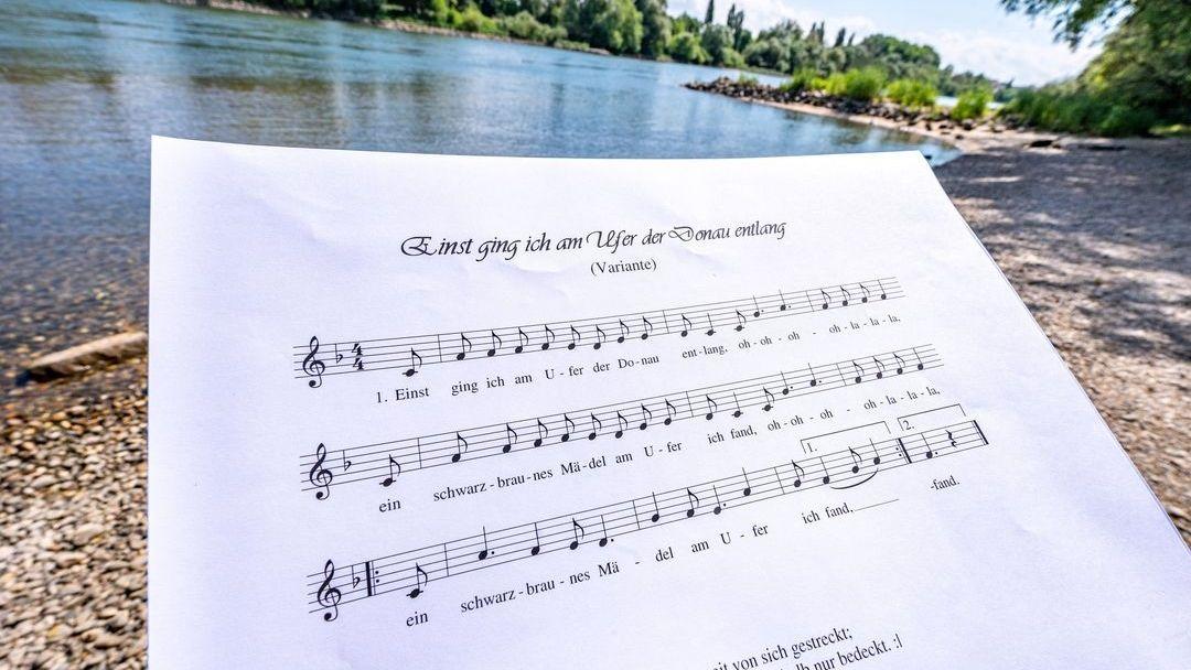 Ein Notenblatt mit dem Liedtext des Donaulieds am Donauufer