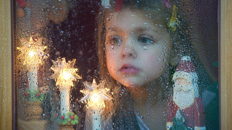 Ein Mädchen schaut am zweiten Weihnachtsfeiertag aus einer vom Regen nassen Fensterscheibe.