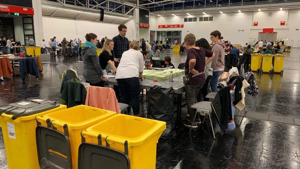 Blick auf einen Tisch für die Wahlhelfer, im Vordergrund leere Tonnen, in die die Stimmzettel eingeworfen wurden.
