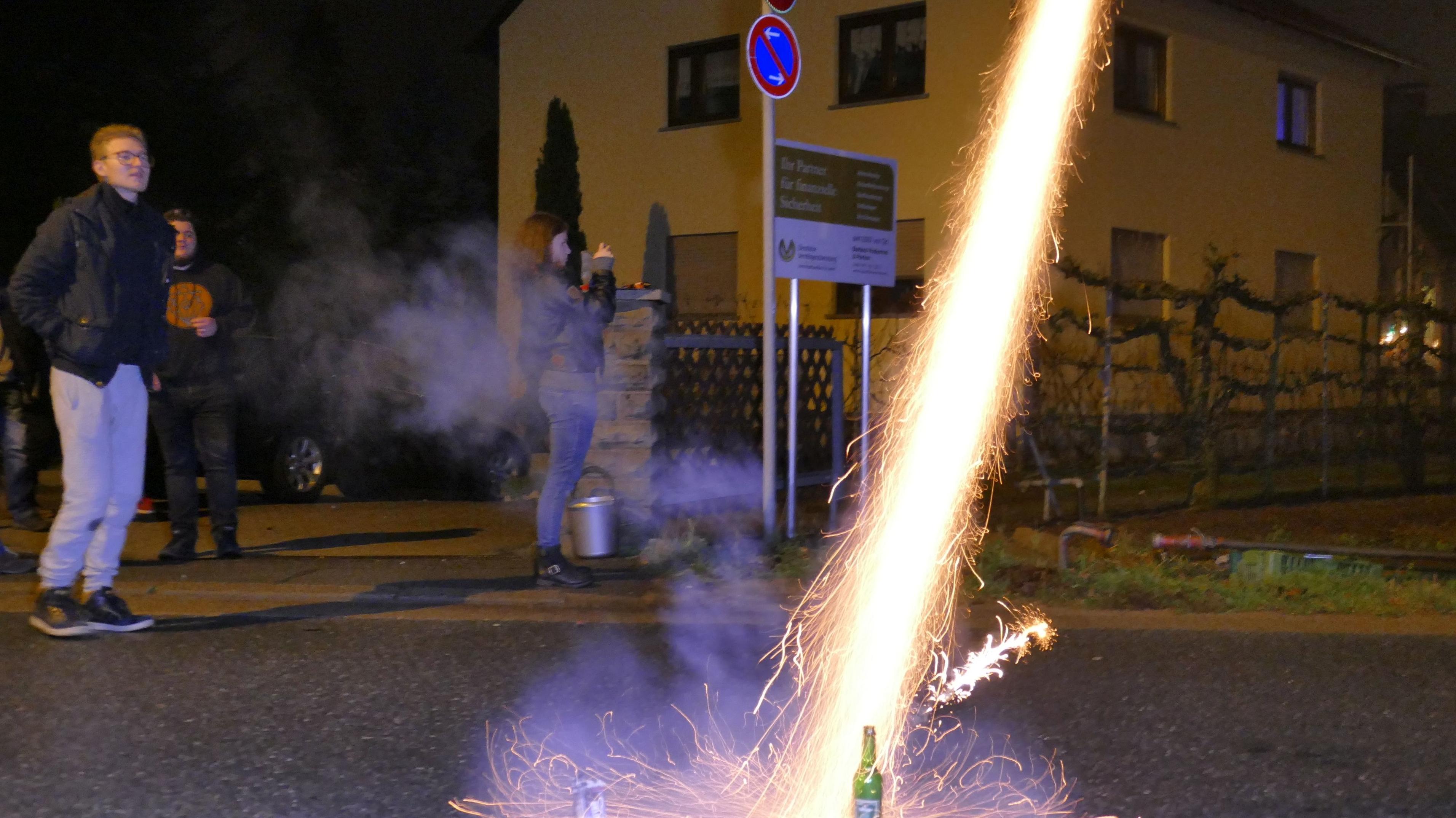 Junge Menschen zünden Silvester-Rakete