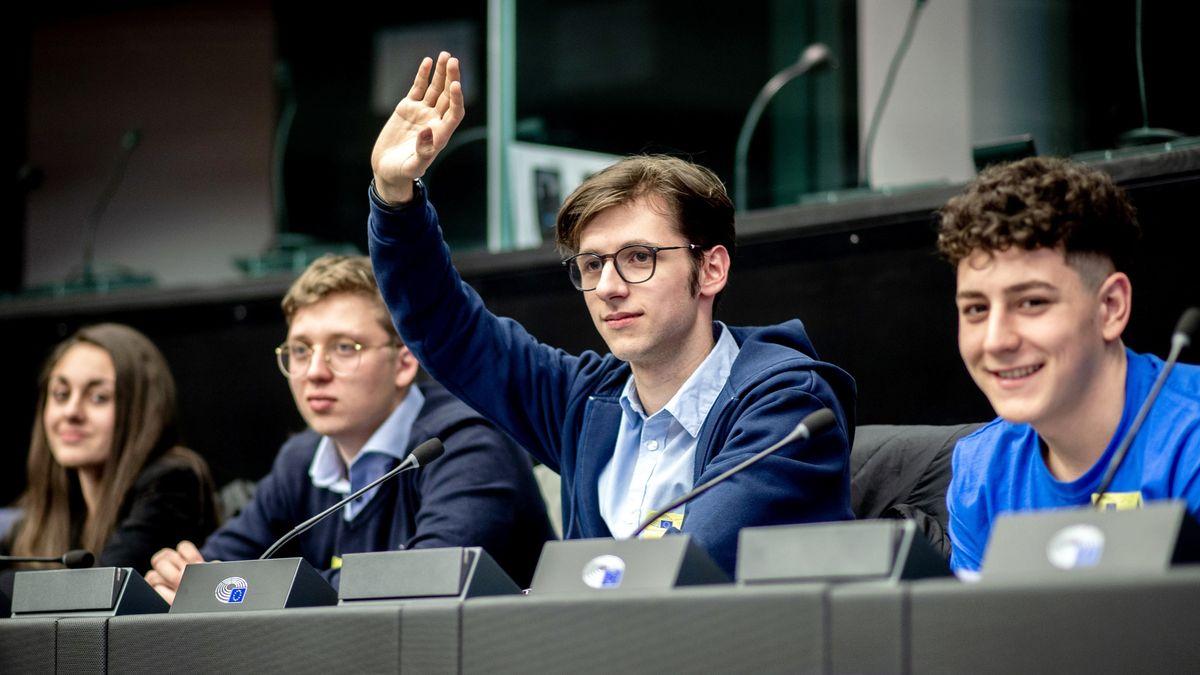 Vier Jugendliche sitzen in einem Hörsaal, Konferenzzentrum oder Parlament. Einer von ihnen meldet sich per Handzeichen zu Wort.