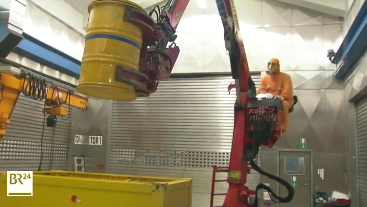 Ein Arbeiter in Schutzkleidung hebt mit einem Kran ein gelbes Fass mit radioaktiven Müll.