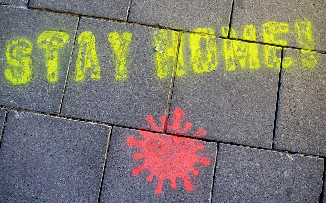 """15.03.2020, Bayern, München: Ein Graffiti bestehend aus dem Text """"Stay Home"""" und einer symbolischen Virusdarstellung ist in der Fußgängerzone auf den Boden gesprüht worden. Bundesweit sollen die nächsten Wochen die Schüler zu Hause bleiben. Foto: Sven Hoppe/dpa +++ dpa-Bildfunk +++"""