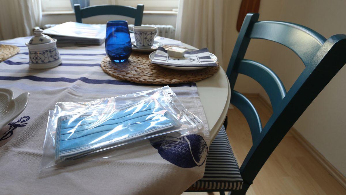 Bayern, Lindau: Eine Packung mit medizinischem Mundschutz liegt auf dem gedeckten Tisch einer Ferienwohnung.
