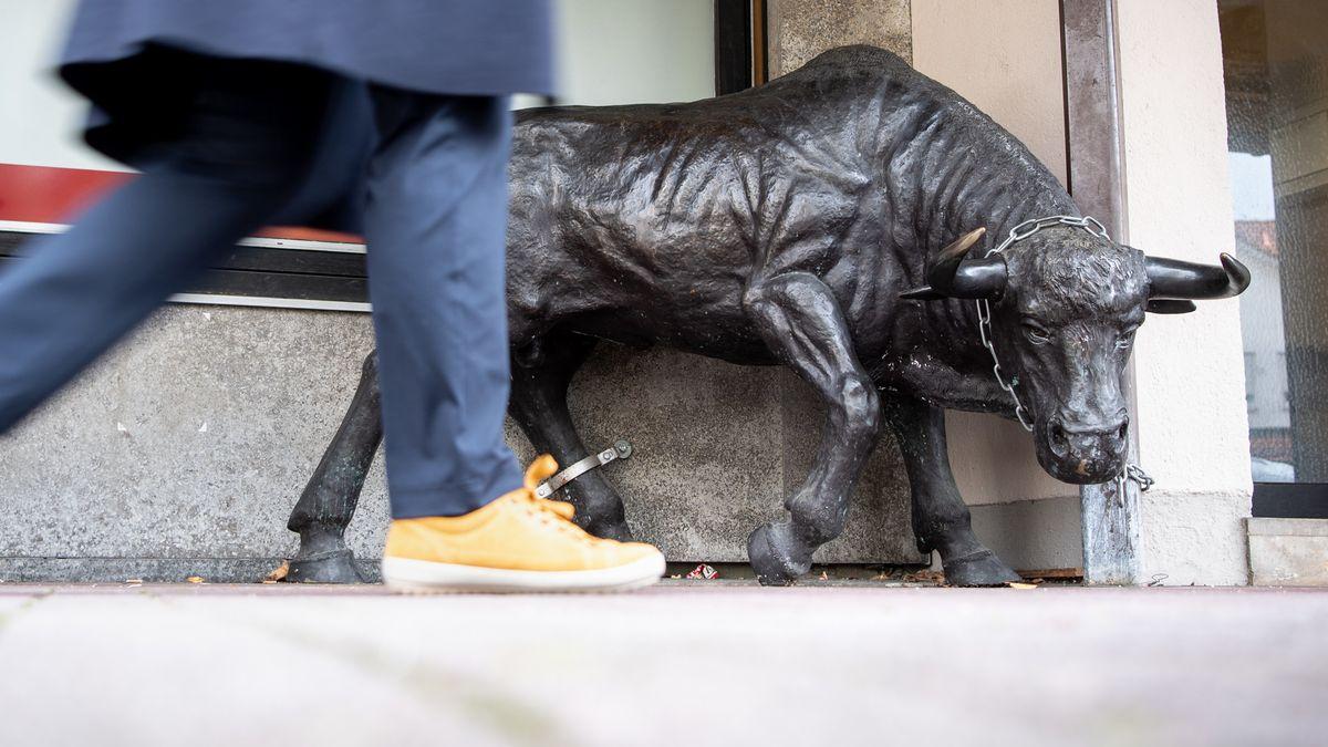 Eine Stier-Skulptur aus Bronze steht vor einer Metzgerei in Krailling. Passant geht vorbei.