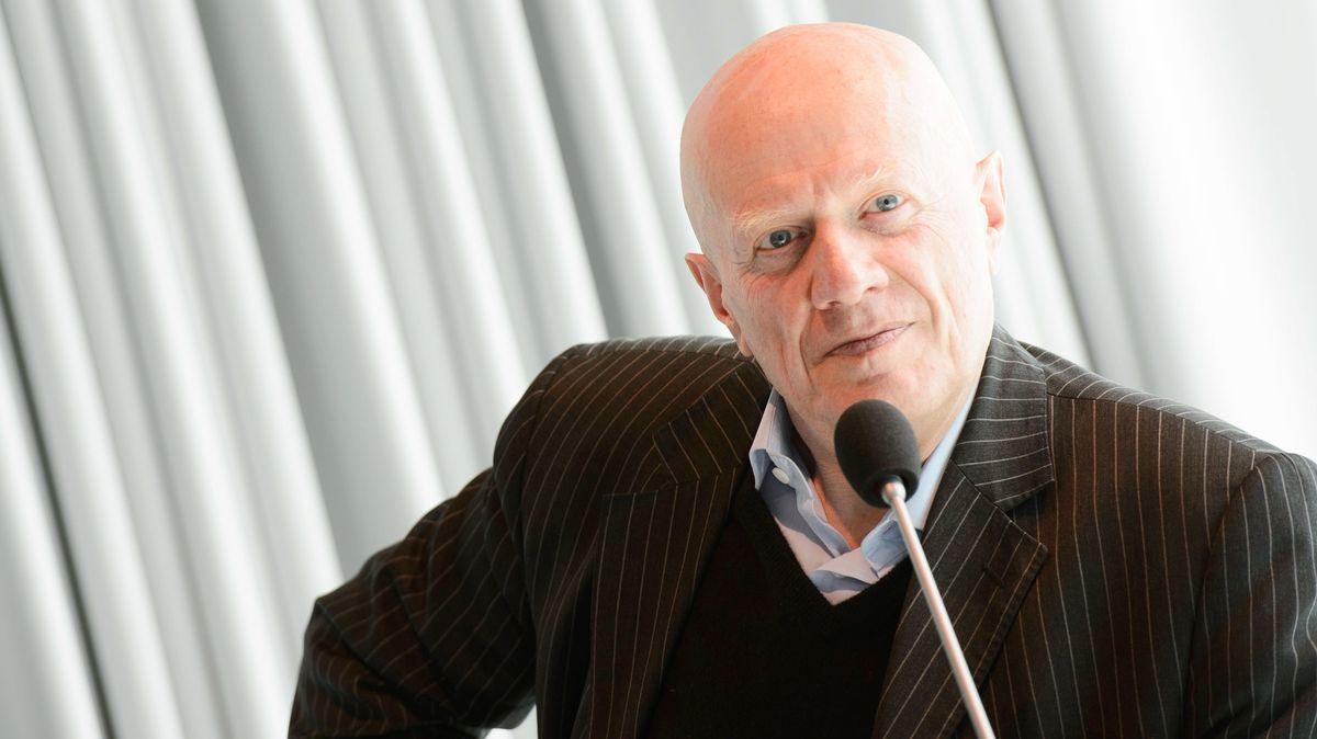 Autor Ralf Fücks sitzt im braunen Nadelstreifenanzug vor einem Mikrofon, er lehnt sich auf linken Arm