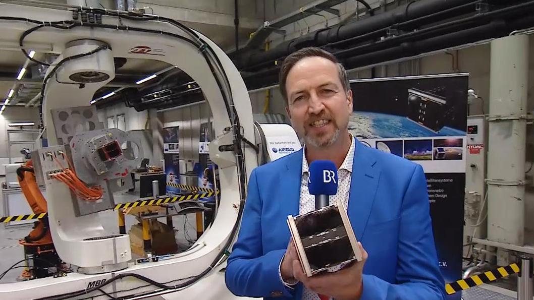 Reporter Sascha Hack mit einem Kleinstsatelliten des Zentrums für Telematik (ZFT) in Würzburg