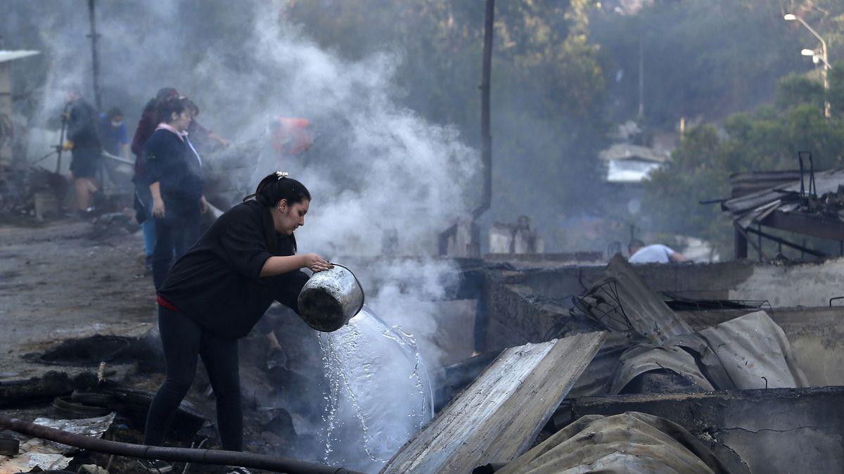 Einwohner der chilenischen Stadt Valparaiso schütten Wasser auf die qualmenden Überreste von Häusern, die bei einem Brand zerstört wurden.