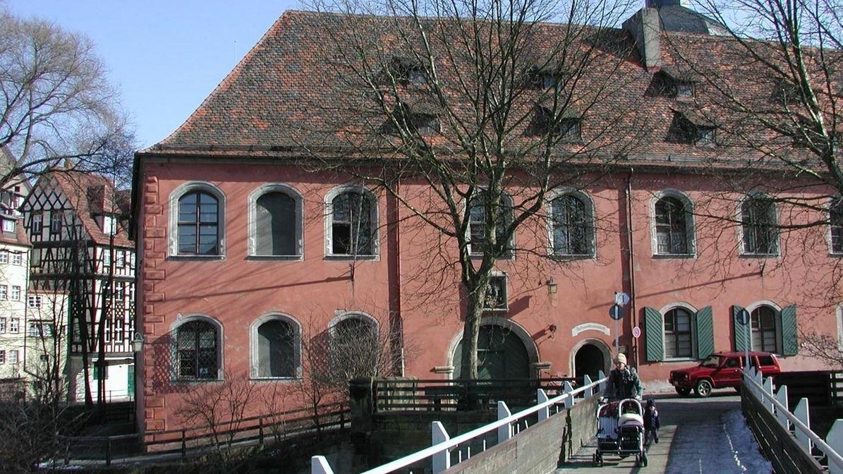 Die rote Fassade von Schloss Geyerswörth in Bamberg, von der Brücke aus gesehen, auf der eine Frau mit einem Kinderwagen unterwegs ist.