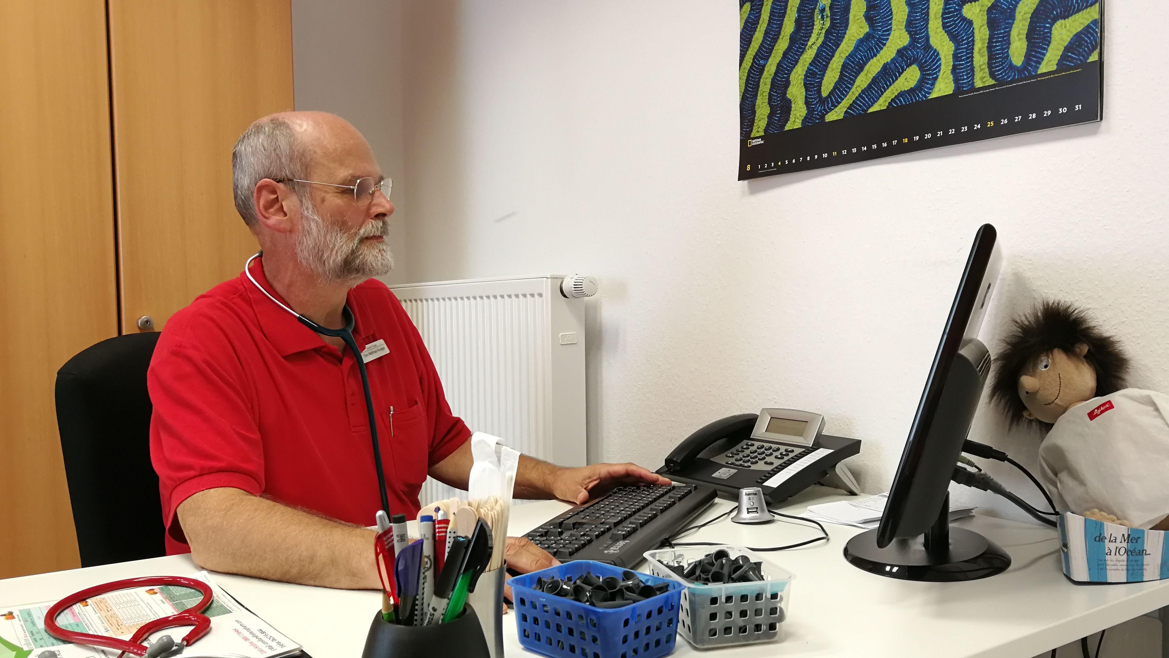 Kinderarzt Dr. Matthias Krueger an seinem Schreibtisch